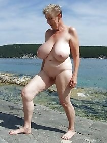 Busty granny posing solo on the sea