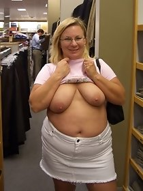 Busty blonde undresses in a clothing store